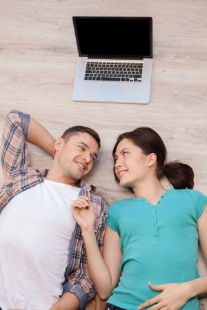 Love connecting people. Top view of beautiful young couple lying down on the floor and looking at each other while laptop lying upon their heads photo