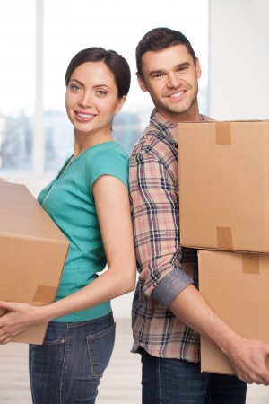 Moving to a new house. Cheerful young couple standing close to each other and smiling at camera while holding cardboard boxes photo