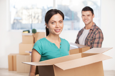 Unpacking at their new house. Beautiful young woman holding an opened cardboard box and smiling at camera while cheerful man standing on background photo