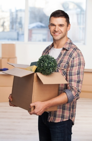 Just moved in a new house. Handsome young man holding an cardboard box with home stuff in it and smiling while more carton boxes laying on background photo