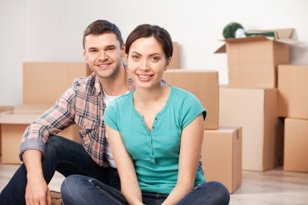 Together in a new apartment. Cheerful young couple sitting close to each other and smiling while cardboard boxes laying on background photo