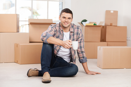 Just moved in a new house. Cheerful young man sitting on the floor and holding coffee cup while cardboard boxes laying on the background photo