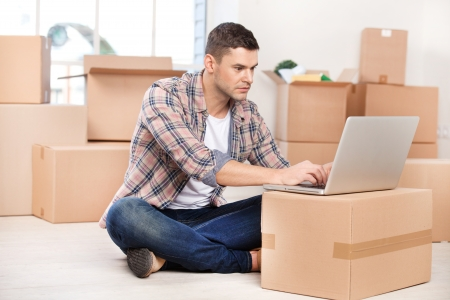 brand new: Working in brand new house. Concentrated young man sitting on the floor and working on laptop while cardboard boxes laying on the background