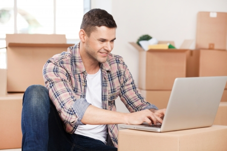 moving company: Searching a good moving company. Cheerful young man sitting on the floor and typing something on laptop while cardboard boxes laying on the background