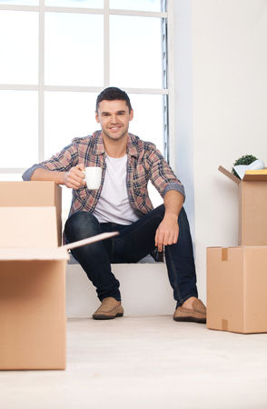 only man: Just moved in a new house. Cheerful young man sitting on the window sill and holding coffee cup while cardboard boxes laying near him