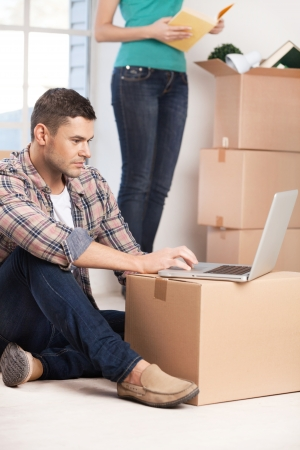 Surfing the net in a brand new house. Confident young man sitting on the floor and working on laptop while woman unpacking a carton box on the background photo