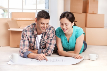 Examining a house plan. Cheerful young couple lying on the floor and looking at the blueprint while cardboard boxes laying on the background  photo