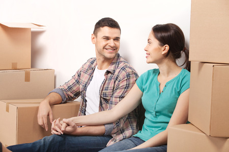 Just moved in a new apartment. Beautiful young loving couple sitting on the floor and holding hands while cardboard boxes laying around them  photo