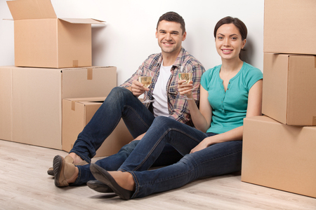 Celebrating a new dwelling. Beautiful young loving couple sitting on the floor and holding glasses with wine while cardboard boxes laying around them  photo
