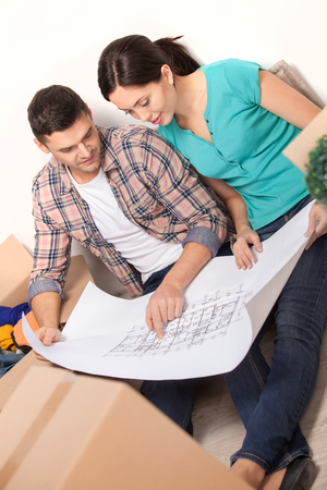 Planning a house improvement. Top view of young couple sitting on the floor and looking at the blueprint while cardboard boxes laying around them  photo