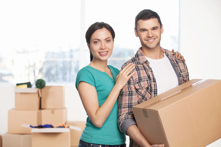 Moving to a new house. Cheerful young couple standing close to each other and smiling at camera while man holding a cardboard box photo