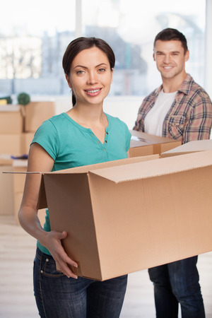 Unpacking boxes. Attractive young woman holding an opened cardboard box and smiling at camera while cheerful man standing on background photo