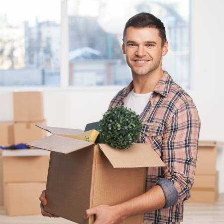 Just moved in a new apartment. Cheerful young man holding an opened cardboard box and smiling at camera while more carton boxes laying on background photo