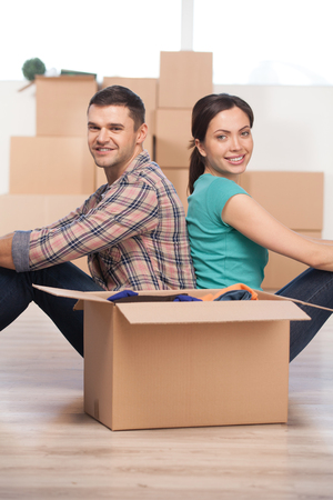 Together in a new house. Beautiful young couple sitting close to each other and smiling while cardboard boxes laying all around them photo