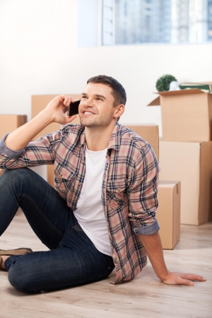 Calling from a new apartment. Handsome young man sitting on the floor and talking on the mobile phone while cardboard boxes laying on the background photo