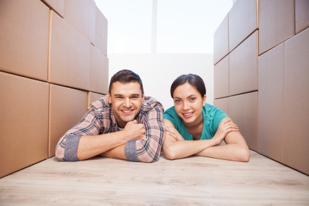 Just moved in a new house. Cheerful young couple lying on the floor between two carton box stacks   photo