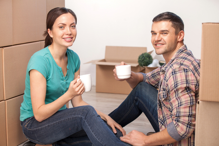 Relaxing in new house. Cheerful young couple sitting on the floor and drinking coffee while cardboard boxes laying all around them  photo