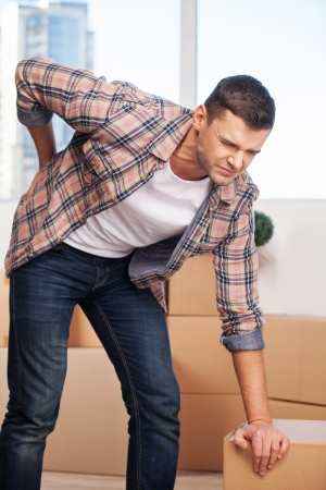 dolor de espalda: Dolor en la espalda. Hombre joven que sostiene la mano en su espalda y expresar negatividad, mientras que apoyado en la caja de cartón Foto de archivo