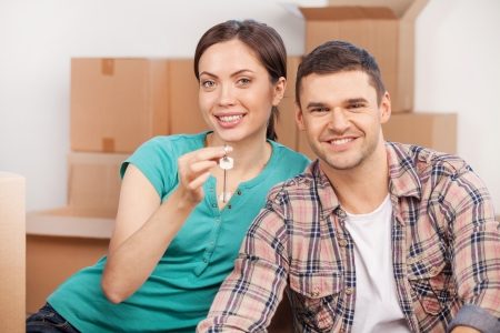 Key of new house. Beautiful young couple sitting close to each other and smiling while holding key from the house photo