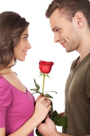 passion couple: Cheerful young loving couple holding a red rose and smiling while standing face to face and isolated on white background