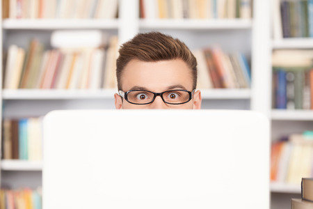 shock: Shocked young nerd man in glasses looking out of computer while sitting at the library