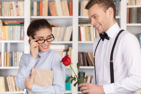 Cheerful young nerd man giving a red rose to a beautiful young woman in glasses while standing at the library Stock Photo - 24939780