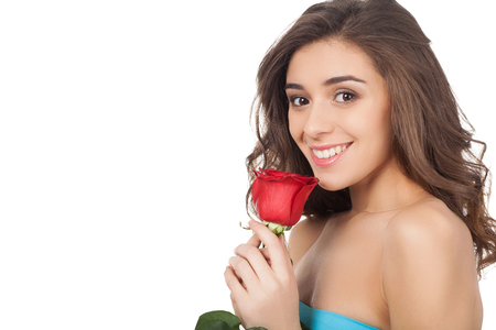 Attractive young woman holding a red rose and smiling at camera while standing isolated on white background photo
