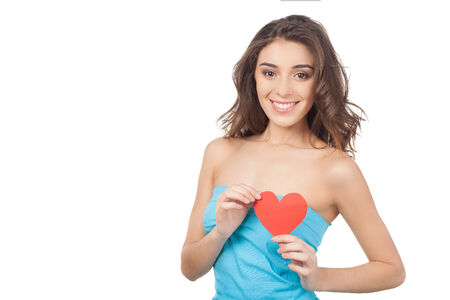 Beautiful young woman holding a red paper heart and smiling at camera while standing isolated on white background photo