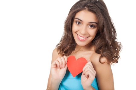 I am in love. Attractive young woman holding a red paper heart and smiling at camera while standing isolated on white background photo