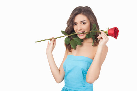 Attractive young woman holding a red rose in her mouth and smiling while standing isolated on white  photo