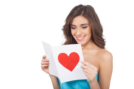 Attractive young woman reading a valentine card while standing isolated on white background Stock Photo - 24939831