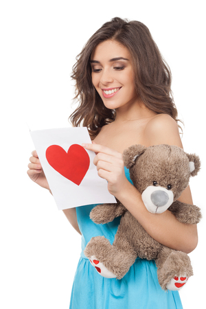 Beautiful young woman reading a valentine card while standing isolated on white background photo