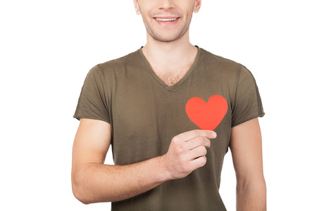Love symbol. Cropped image of young man holding a paper heart while standing isolated on white background photo
