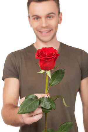 Handsome young man stretching out a red rose and smiling while standing isolated on white background photo