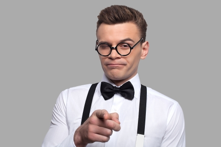 Portrait of young nerd man in bow tie and suspenders pointing camera while standing against grey background