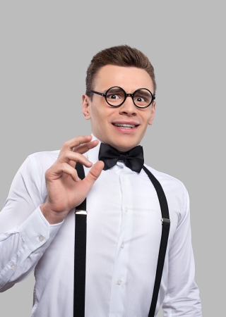 afraid man: Terrified young nerd man in bow tie and suspenders making a face and gesturing while standing against grey background