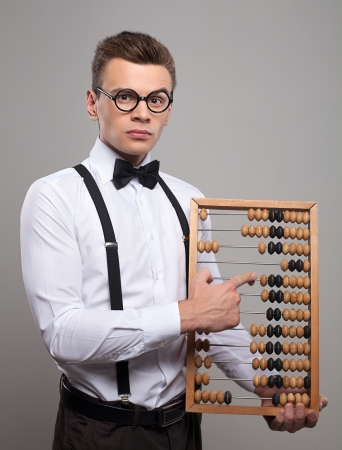 Serious young man in bow tie and suspenders holding abacus and pointing it while standing against grey background photo