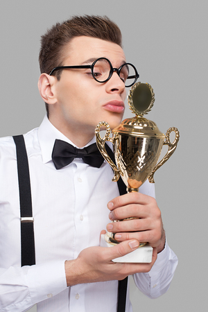 Young man in bow tie holding a trophy and kissing it while standing against grey background  photo