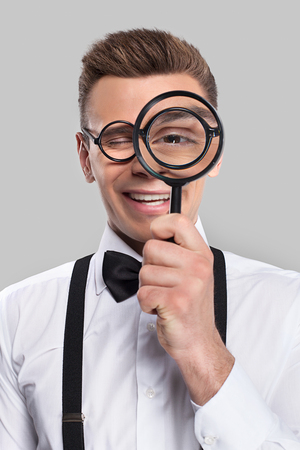 Magnifying you. Portrait of cheerful young man in bow tie and suspenders holding magnifying glass in front of his eye and smiling photo
