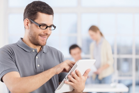 Cheerful young businessman in casual wear working on digital tablet and smiling while his colleagues communicating