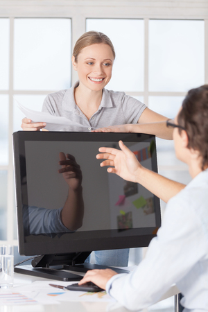 We have this contract. Young man in shirt sitting at the computer and gesturing while woman leaning at the computer monitor and holding a paper photo