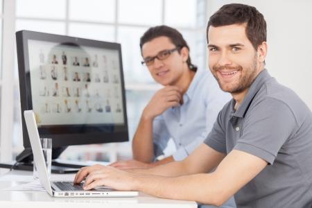 people  camera: El personal de TI. Dos hombres j�venes alegres sonriendo a la c�mara mientras se est� sentado en frente de los monitores de ordenador Foto de archivo