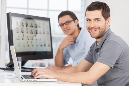 people  camera: IT staff. Two cheerful young men smiling at camera while sitting in front of computer monitors Stock Photo