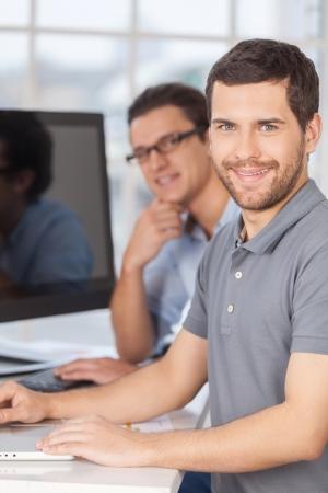 business support: Succesvolle IT-personeel. Twee vrolijke jonge mannen glimlachend in de camera tijdens de vergadering in de voorkant van computermonitoren