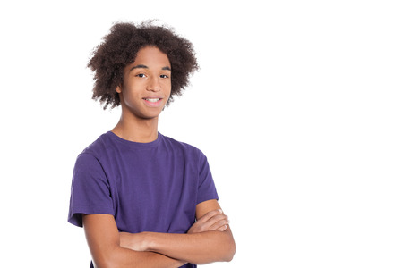 Confident teenager. Smiling African teenage boy keeping arms crossed and smiling while standing isolated on white