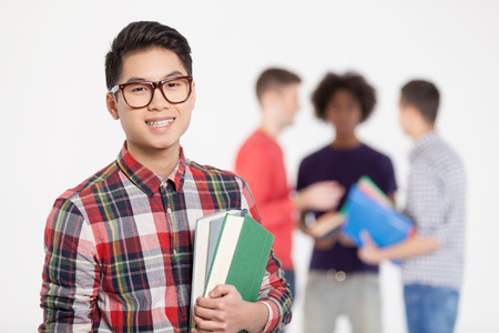 Smart and confident. Cheerful Chinese teenage boy in glasses holding books and smiling while his friends standing on background photo