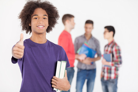 thumbs up group: I love studying! Cheerful African teenage boy holding books and gesturing while his friends standing on background Stock Photo