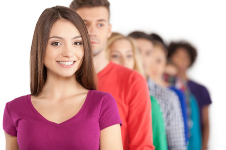 Standing in a row. Young people standing in a row while beautiful young woman standing in front of them and smiling photo