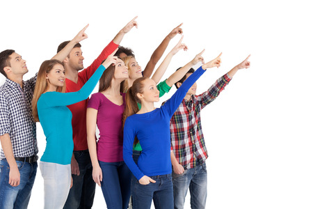 Is it a plane? Group of cheerful young multi-ethnic people standing close to each other and pointing away while standing isolated on white photo
