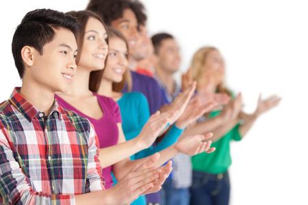 aplaudiendo: Aplausos. Grupo de jóvenes alegres pueblo multiétnico de pie en una fila y aplaudiendo a alguien mientras está de pie aislado en blanco Foto de archivo